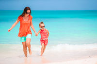 Beautiful mother and daughter at Caribbean beach enjoying summer vacation.