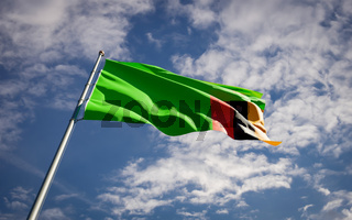 Beautiful national state flag of Zambia fluttering at sky background. Low angle close-up Zambia flag 3D artwork.
