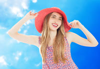 Portrait of a beautiful woman in a straw hat. Laughing girl. Summer time blue sky background