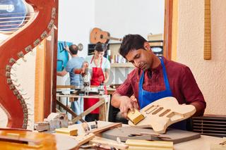 Lehrling in Werkstatt vom Gitarrenbauer
