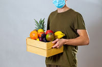 Man with face mask giving wooden box with fruit and vegetable to customer