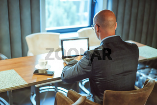 Businessman using digital wireless technology. Rear view of successful Caucasian man working with laptop computer at workplace against window