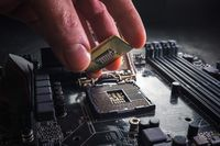 Technician plug in CPU microprocessor to motherboard socket. Workshop background. PC upgrade or repair concept.