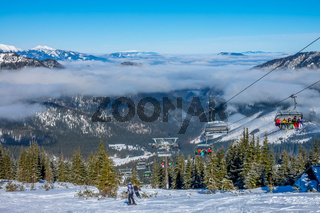 Skiers on the Chair Lift and Light Fog between Peaks
