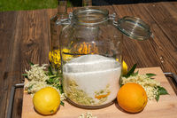 Large preserving jar with the ingredients for elderflower liqueur
