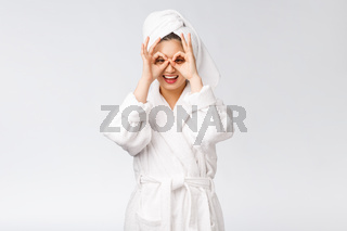 Close up of young smiling woman with finger ok gesture on eyes, isolated on white background