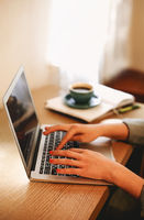 Crop woman using laptop working at home