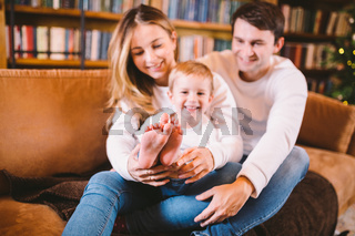 Happy family on sofa near bookcase and Christmas tree in evening. Cozy family atmosphere at christmas time . Enjoyng love hugs, holidays people. Togetherness concept. Home holiday living room