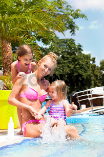 Happy family in the pool, having fun, vacation concept