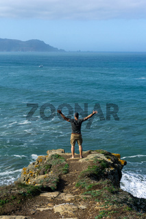 man celebrating the view at the cliffs of Loiba in Galicia