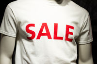 Male upper body dummy in a shop display with the word SALE written on it. Consumerism and low price concept.