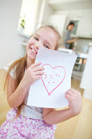 Mädchen zeigt Papier mit rotem Herz