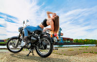 An attractive girl on a motorbike posing outside