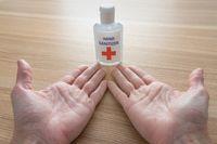 Using a bottle of hand sanitizer against viruses.