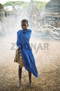 TOPOSA TRIBE, SOUTH SUDAN - MARCH 12, 2020: Kid in skirt wrapping in dotted blue fabric against smoke and huts in Toposa Tribe village in South Sudan, Africa