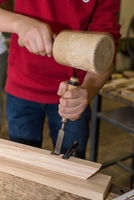 Carpenter works with a mallet and chisel - craftsman