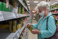 Senior woman with face mask shops in the supermarket