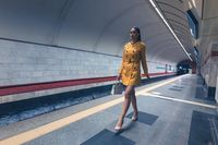 Walking on subway platform beautiful young girl with long beautiful legs in a yellow spring coat and a white handbag or purse in hand