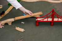 A boy collects a toy railway with a bridge to the floor. Wooden details of the designer. Educational games for children.