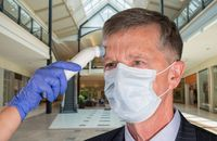 Senior man wearing face mask having temperature taken to check for virus at shops