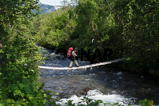 Young woman hiker with backpack behind her shoulders crossing mountain river on suspension bridge