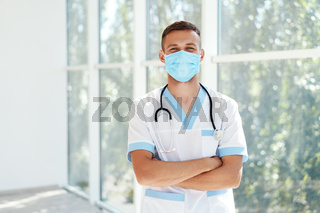 Confident male doctor wearing medical mask with arms crossed in hospital background