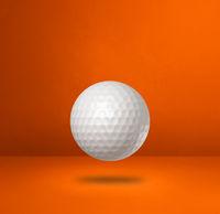 White golf ball on a orange studio background