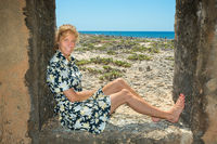 Dutch woman sits in window frame on beach