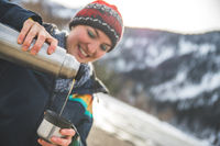 Outdoor wilderness adventure: Caucasian girl is drinking a metal cup of tea