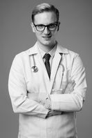 Young handsome man doctor with blond hair against gray background