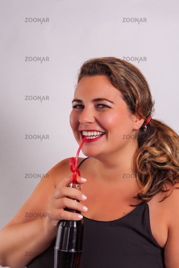Woman laughingly drinks from a bottle