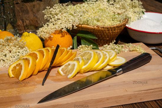 A cutting board with a vanilla pod, a sliced organic lemon and organic orange and elderflower