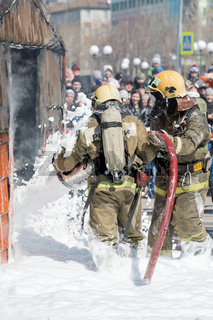 Firefighters extinguishing fire from fire hose, using fire-fighting water-foam barrel with air-mechanical foam