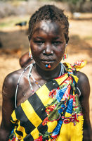 BOYA TRIBE, SOUTH SUDAN - MARCH 10, 2020: Woman in traditional colorful clothes and accessories with ritual piercing and scar modifications looking at camera in tribe settlement in South Sudan