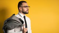 Handsome serious business man with trendy beard dressed in greyish suite posing holding his jacket on his shoulder hanging it behind looking isolated on yellow background