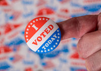 Finger with I Voted Today sticker in front of background created from many election voting badges