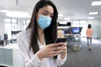 Businesswoman wearing face mask using smartphone at modern office