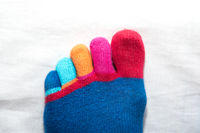 funny colorful toes of hand-knitted sock - close-up