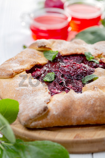 Sweet open pie with red plums.