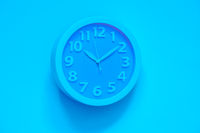 Cyan clock on pink painted wall. Minimal time concept. Chrismas eve or new year idea. Stylish analog clock hanging on wall, space for text
