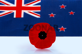 A remembrance day poppy flower with a Australian Flag on the background.