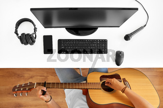young man with computer playing guitar at table