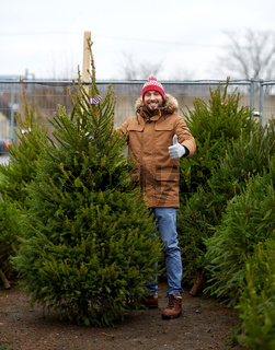 happy man buying christmas tree at market