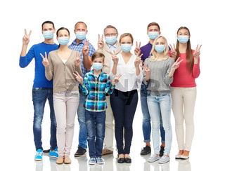 people in medical masks showing peace hand sign