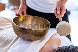Woman getting a sound massage with singing bowls