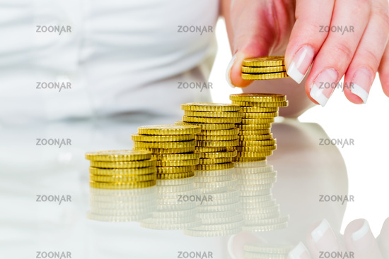 Woman with coin stack saving money