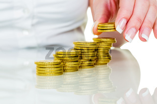 Frau mit Münzstapel beim Geld sparen