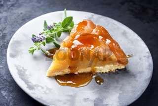Traditional French tarte tatin with apples and vanilla offered as close-up on a modern design plate with rustic background