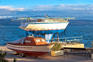 Sailboat and small boat on dry dock by the sea