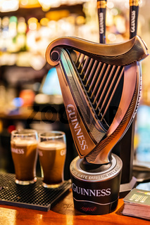 Selective focus on Guinness tap with blurred pints of foamy beer